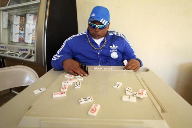 The dead body of Jomar Aguayo is seated at a table with domino tiles and with a condom placed in one of his hands in San Juan