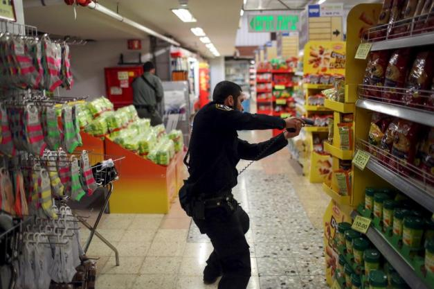 An Israeli policeman searches a supermarket inside the Central Jerusalem Bus Station after police said a woman was stabbed by a Palestinian outside the bus station