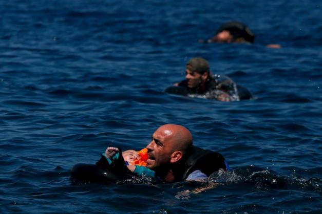 A Syrian refugee holding a baby in a lifetube swims towards the shore after their dinghy deflated some 100m away before reaching the Greek island of Lesbos