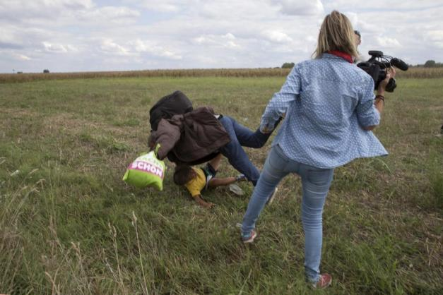 A migrant carrying a child falls after tripping on TV camerawoman Laszlo while trying to escape from a collection point in Roszke village, Hungary