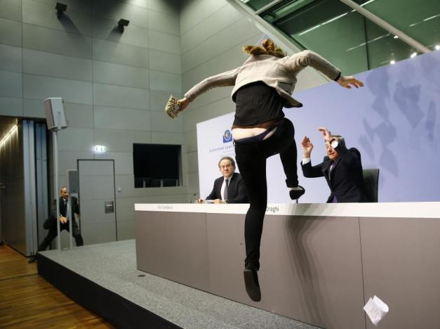 A protester jumps on the table in front of the European Central Bank President Draghi during a news conference in Frankfurt